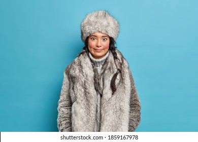 Suprised inuit woman with rouge cheeks looks wondered at camera has two combed pigtails wears grey fur hat and coat prepared for severe cold winter not to feel frozen poses against blue background.