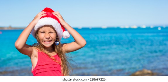 Suprised little girl in christmas hat during beach vacation