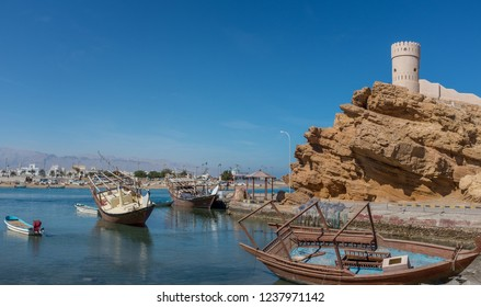 SUR, OMAN - DECEMBER 31, 2015: Wooden dhow boats at a watchtower in the Al Ayjah district of Sur, Oman