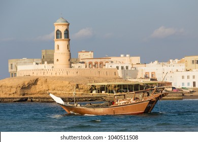 SUR, OMAN - NOVEMBER 25, 2017: Lighthouse and traditional boat in the bay of Sur, Oman