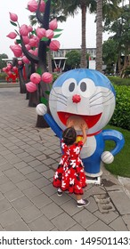 Surabaya / Indonesia - January 12, 2019 : little girl playing outdoor with doraemon artificial