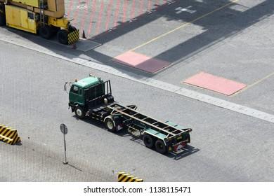 Surabaya, Indonesia - July 2, 2018: Truck passes to go to loading and unloading the container at port of Surabaya Petikemas Terminal (TPS), Tanjung Perak, Surabaya, East Java, Indonesia