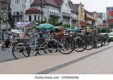 Surabaya, Indonesia - JUNE 7, 2019: view of several pedicabs waiting for passengers on the side of a public road.