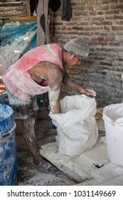 Surabaya, Indonesia - November, 04, 2017: Workman prparing krupuk in a little factory in Jav Indoensiadrying in the sun