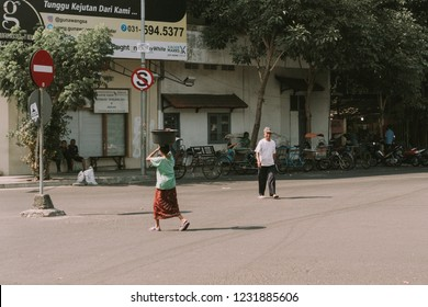 Surabaya, Indonesia - October 13, 2018: An old woman dressed in traditional clothes and carrying items in bucket above her head and old man, cross the road.