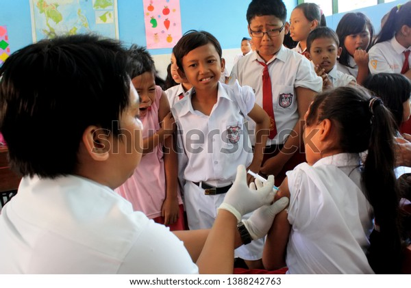 Surabaya-Indonesia, December 11, 2013. A health worker is giving an injection of vaccine to prevent diphtheria virus in elementary school students. this action is the concern of the Surabaya city gove