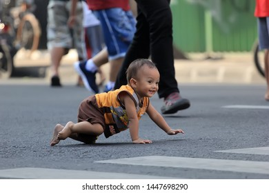 surabaya-indonesia.13 December 2015. a child is crawling playing alone on the road. as parents must be careful to let their children play alone on the road.
