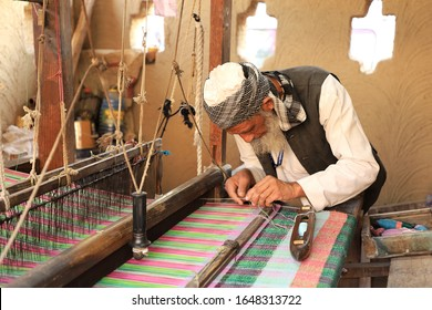 Surajkund, Faridabad, Haryana, India - February 14, 2020 - An old man weaving a carpet during the 34th Surajkund International Crafts Mela. The festival has over 1 million visitors every year.