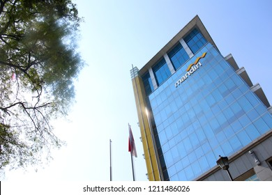 Surakarta 23 Oct 2018 - Indonesia's bank called Mandiri built their own building with yellow sign and blue color glass with a nice view of sky and trees in Surakarta which taken during morning day