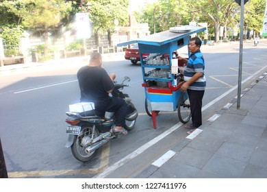 Surakarta 23 Oct 2018 - Street food vendor is selling their ice cream to a guy who wear black t-shirt and ride a scooter during hot day in Solo