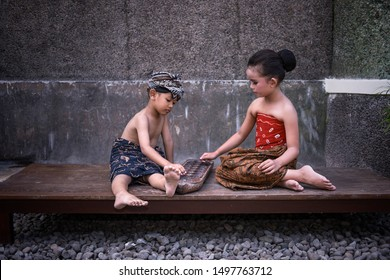Surakarta, Indonesia, April 14, 2019. Two small children were playing the Dakon game, the old children's game, at the home of Ndalem Djimatan, Batik Laweyan Village, Solo, Central Java, Indonesia.