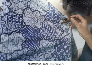 SURAKARTA INDONESIA, JUNE 17 2018 : Close Up Hand Painting Batik on the Blue Fabric. Batik Tulis