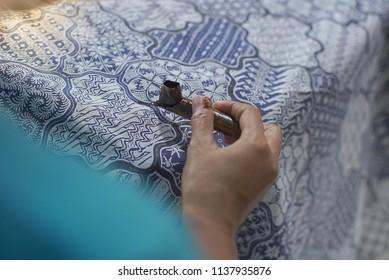 SURAKARTA INDONESIA, JUNE 17 2018 : Close Up Hand Painting Batik on the Blue Fabric. Batik Tulis