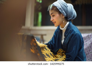 SURAKARTA JUNE 17 2019 : Tourist making batik with canting on the gold fabric bokeh background. Batik Tulis in Solo Indonesia