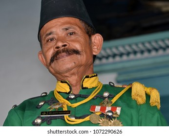 SURAKARTA (SOLO), JAVA/INDONESIA - OCT 31, 2013: Elderly non-commissioned officer guards the Sultan's palace (kraton) and wears a green traditional uniform with black peci cap, on Oct 31, 2013.