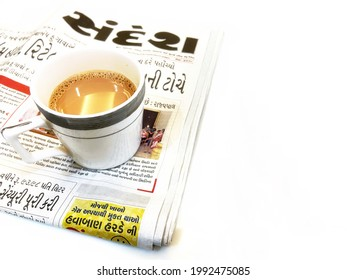 surat, gujarat - june 15 2021: 'sandesh' newspaper with hot tea on a white table. morning time. selective focus.