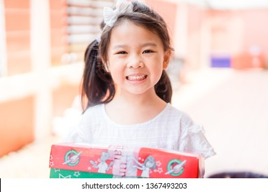 SURATTHANI, THAILAND - December 25, 2018 : Little thai girl  have received gift box from Samaritan's purse at Church in Christmas time.