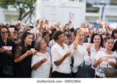 SURATTHANI, THAILAND - OCTOBER 16 : Crowds of mourners hold Thai cash for show picture of King Bhumibol during mourning ceremony at Suratthani City Hall on October 16, 2016 in Suratthani, Thailand.