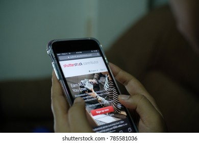 SURATTHANI, THAILAND - October  2,2017: Woman hand holding Apple iPhone7 plus with Shutterstock application on the screen. Shutterstock  is a Stockphoto app for smartphones.