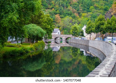 Sure river in Esch-sur-Sure, Luxembourg, with reflections and green vegetation at one side and the stone wall and road in the other side