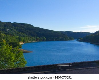 Sure river in Lultzhausen, Esch-sur-Sure, Luxembourg. Beautiful landscape with green mountains and a bench in the foreground