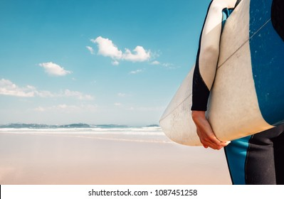 Surf board in surfer's hand close up image with oceans waves view