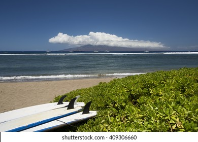 Surf boards lying on beach with the island of Lanai. Lahaina, Maui, Hawaii