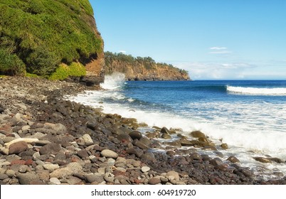 Surf crashes into rocky shore and cliffs of Kohala, eroding cliffs. North coast of the Big Island of Hawaii, the Pacific ocean and blue sky on a sunny day. View from  Pololu Valley beach in February.