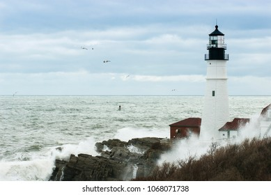 Surf creates huge waves crashing by Portland Head lighthouse as sun break through clouds in after late winter storm passes by. Unique high tides.