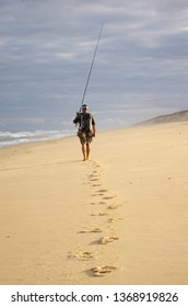 Surf fisherman with his fishing rod walking in the sand on a beach of Atlantic ocean. Adventure fishing, wild fishing