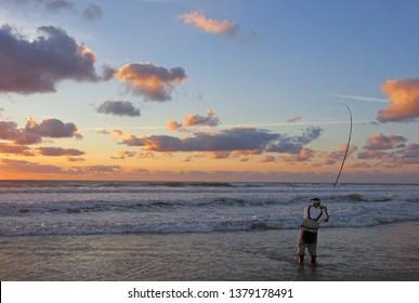 Surf fisherman into the waves. Sea fishing