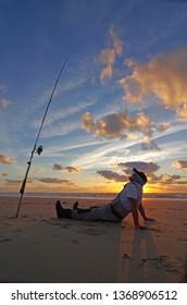 Surf fisherman waiting for fish, night fishing