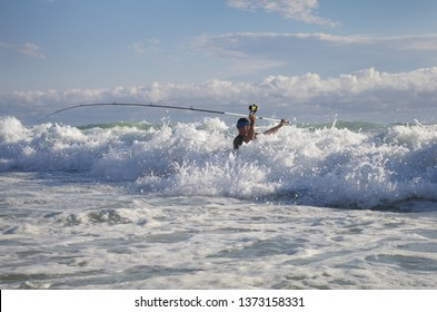 Surf fisherman in the waves. Surf fishing scene