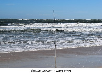 Surf fishing pole standing at the ocean beach Florida, USA