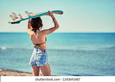 surf girl go to surfing- Beautiful smiling girl surfer looking for the waves. Back view