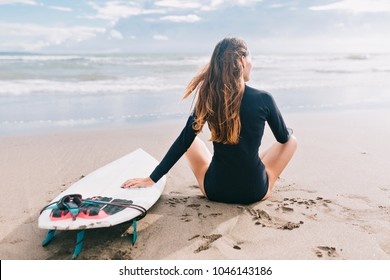 Surf girl with long hair dressed in black swimsuit sitting on the shore of ocean and looking away. Rear view of woman with surfboard on a beach at sunset or sunrise. Ocean and white sand