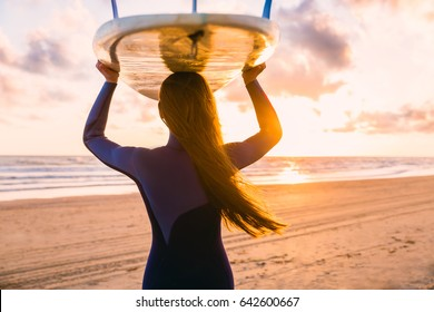 Surf girl with long hair go to surfing. Woman with surfboard on a beach at sunset or sunrise. Surfer and ocean