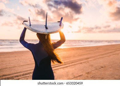 Surf girl with long hair go to surfing. Woman holding surfboard on a beach at sunset or sunrise. Surfer and ocean