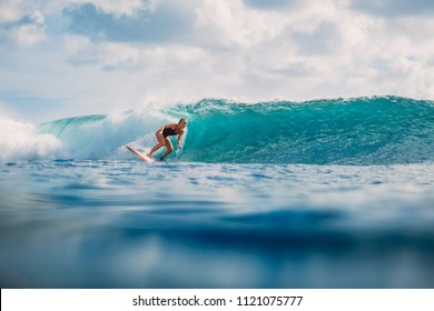 Surf girl on surfboard. Woman in ocean during surfing. Surfer and ocean
