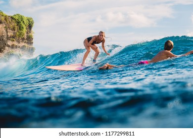 Surf girl on surfboard. Woman in ocean during surfing.
