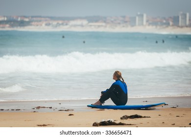Surf girl seat on the board and look to the lineup