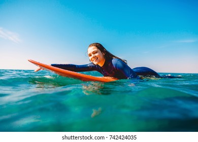 Surf girl is smiling and rowing on the surfboard. Woman with surfboard in ocean. Surfer and ocean