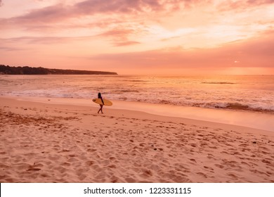 Surf girl with surfboard go to surfing. Surfer woman on beach at bright sunset