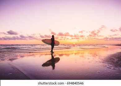Surf girl with surfboard on a beach at colorful sunset. Surfer woman and waves