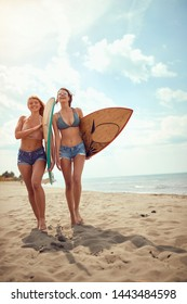 Surf girls go to surfing in ocean. Smiling woman holding surfboard on a beach.