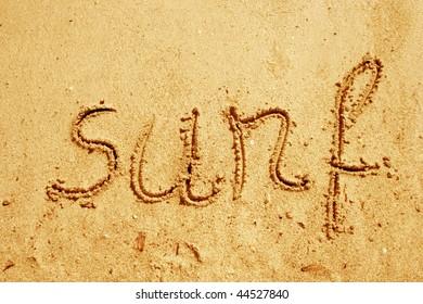 Surf hand written in sand on a beach