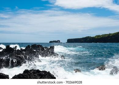 Surf hitting volcanic rocks at the Maui coastline