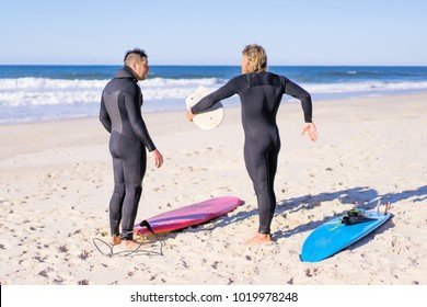 surf instructor with a student on the ocean. Surfer in a wet suit with a training board. Nazare, Portugal.