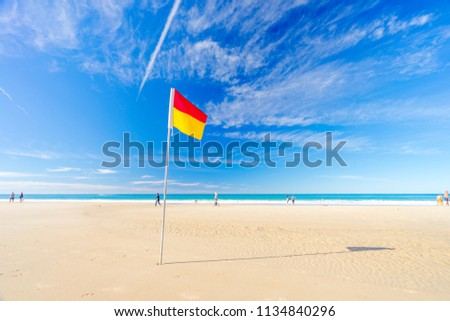 b6e83c5c0a1 Surf life saving flag on the beach with blue water - June 2018 Gold Coast