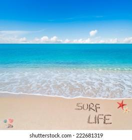 "surf life"" written on a tropical beach"